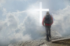 Man walking to the cross. Man on top of the mountain looks to a cross of light. Bright atmosphere royalty free stock photo