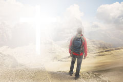 Man walking to the cross. Man on top of the mountain looks to a cross of light. Bright atmosphere stock image