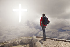 Man walking to the cross. Man on top of the mountain looks to a cross of light. Bright atmosphere royalty free stock image