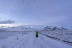 Man walking to mountain on the snow in Iceland. royalty free stock photo