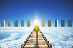Man walking to an open door in clouds concept Royalty Free Stock Images