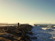 Man walking to the sea on the stones, wave splash Stock Photography