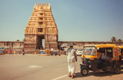 Man walking to 12th century Chennakeshava Temple with carved tower gopuram Royalty Free Stock Photos