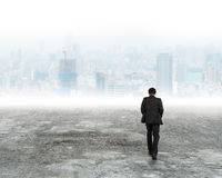 Man walking toward city buildings in mist. Man walking on dirty concrete floor toward city buildings in the mist stock photos