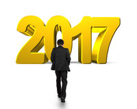 Man walking toward 2017 year. Golden number,  on white background Royalty Free Stock Photo