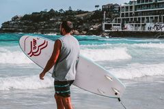 Man Walking Towards Body Of Water Holding A Surfboard Stock Photo