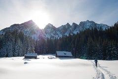 Man Walking Towards Brown Housen in a Snow Place Stock Photos