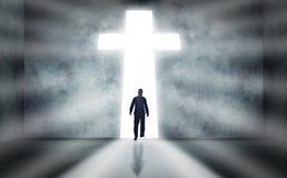 Man Walking Towards Cross. Man walking towards a huge cross passage stock photo