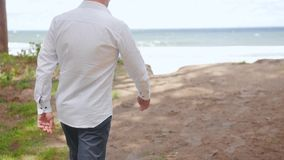 Man walking towards edge of a cliff, looking over the sea. Medium shot. stock video footage