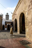 A man walking towards on of the old city gates in Essaouira in Morocco. Royalty Free Stock Images