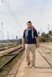 Man walking towards train station backpack travel. Railroad smiling tourist Royalty Free Stock Photo