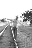 Man walking on the tracks. Black and white image of a man walking on the tracks Stock Photography