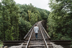 Man Walking on Train Railway in the Middle of the Woods Stock Images