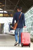 Man walking on train station platform with travel bag Stock Images