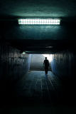 A man walking in the tunnel. Man silhouette walking in white light at end of tunnel Stock Photography