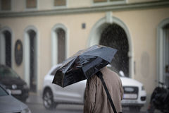 Man walking with umbrella, rear view. This photograph represents a man walking with umbrella, rear view. Useful file for your newspaper weather concept Stock Images