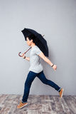 Man walking with umbrella in studio Stock Photo