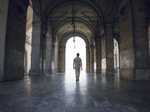Man walking under heavy vaults, in Pisa, Italy. Bright light seeping in.