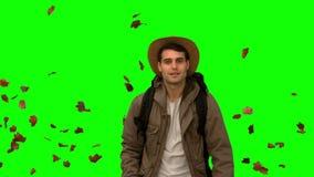Man walking under leaves falling on green screen stock footage