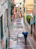 Man walking under the rain in a Genoa's alley. Man with umbrella walking under the rain in a Genoa's alley Royalty Free Stock Images
