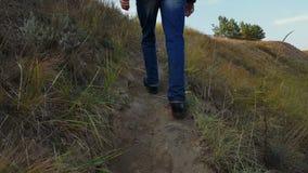 Man is walking up an earthen path stock video footage