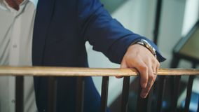 A Man Walking Up the Stairs Holding the Bannister. A man walking up the stairs and holding the bannister. Wedding preparation. Close-up shot royalty free stock photos