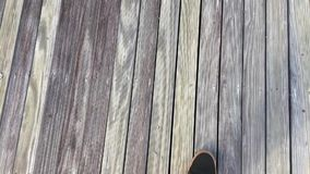 Man walking on vintage wooden board floor. Grunge wooden weathered pine textured planks. Grey rustic fence. HD. stock footage