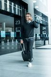 Man walking with wheeled bag. At airport terminal and talking on phone Royalty Free Stock Photo