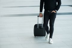 Man walking with wheeled bag. At airport terminal and talking on phone Stock Image