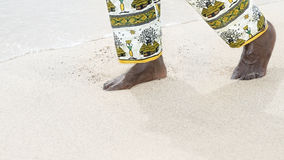 Man walking on a white sand beach Royalty Free Stock Photos