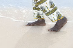 Man walking on a white sand beach Stock Images