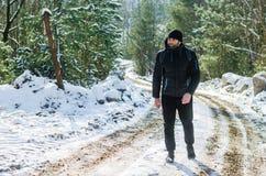 Man walking in winter snowy forest. Man traveler with backpack walking in winter snowy forest Royalty Free Stock Photos