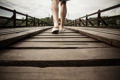 Man walking on a wooden bridge Stock Photo