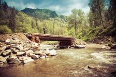 Man walking through a wooden bridge Stock Image