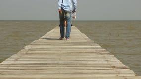 Man Walking on Wooden Dock Toward the Sea stock photos