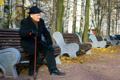 Man with Walkingstick. Old elegant man with walkingstick sitting on a bench Stock Image