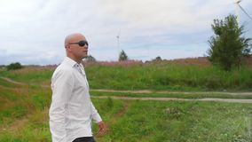 Man walks across the field and sing against the background of wind turbines Energy Production. Medium shot. stock video