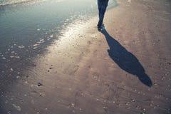 Person walks alone on sandy beach Royalty Free Stock Photo