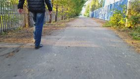 Man walks along the asphalt stock video