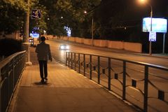 A man walks along the bridge. On the street at night stock photos