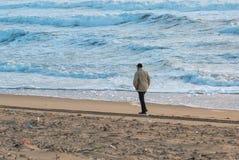 Man Walks Along Coast Royalty Free Stock Photos