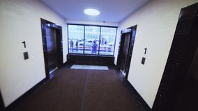 Man walks along empty hallway to elevator view from head cam stock video