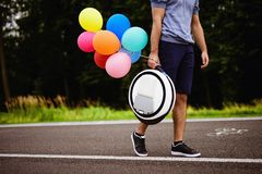 A man walks along the park path with a monoclean in his hands. To it are attached multi-colored inflatable balls Royalty Free Stock Photo
