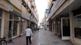 Man walks along pedestrian street with shops and parked bicycles. DUBAI UNITED ARAB EMIRATES - DECEMBER 18 2018: Man walks along narrow Arabian pedestrianized stock video footage