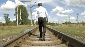 Man walks along railway tracks in the countryside Royalty Free Stock Photos