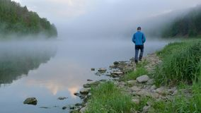 Man walks along river bank with stones past blue water. Calm man walks along river bank with little stones past wonderful blue water with thick morning fog stock footage