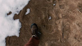 Man walks along the sand in early spring when all the snow has not melted yet. First person view. stock video footage