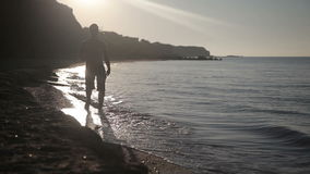 A man walks along the seashore stock video footage