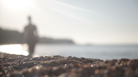 A man walks along the seashore stock footage