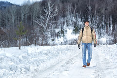 Man walks along a snowy road Stock Images